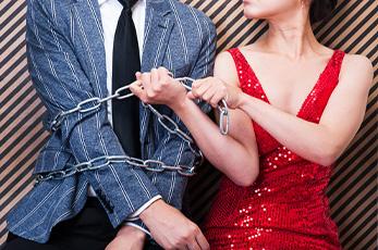 男性を鎖で縛る女性