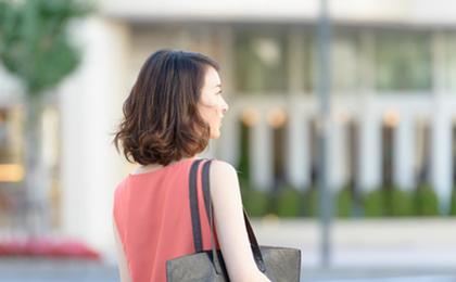 外を歩く後ろ姿の女性